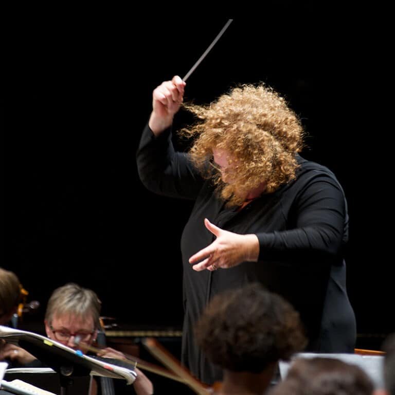 Rosemary Thomson conducting on a podium