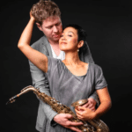 Singer Xin Wang and saxophonist Wallace Halladay in an embrace