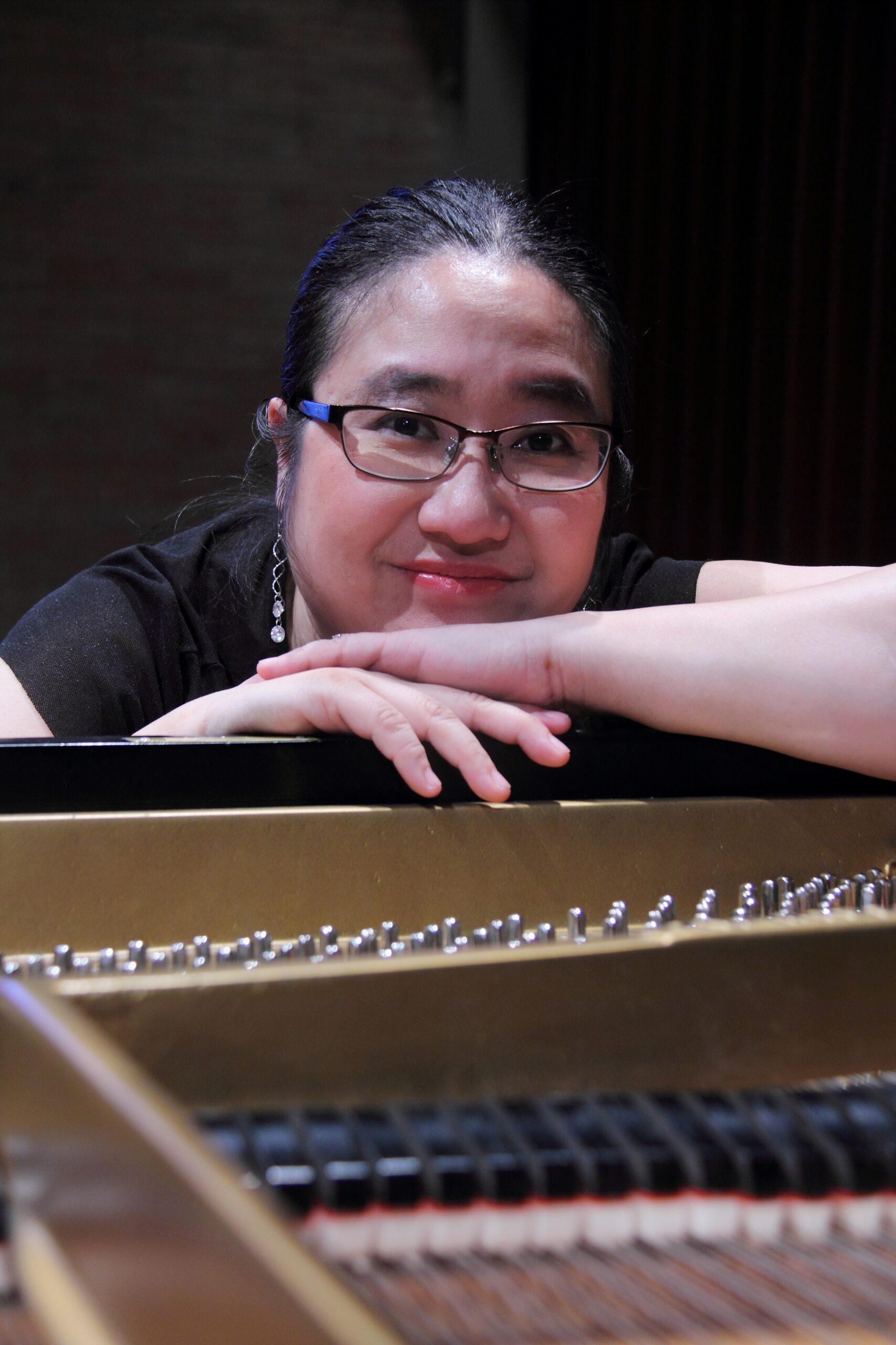 Jennifer Tung leaning on a piano