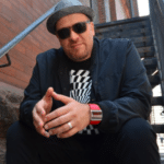 Jazz pianist Robi Botos, wearing hat and sunglasses, sitting on a staircase