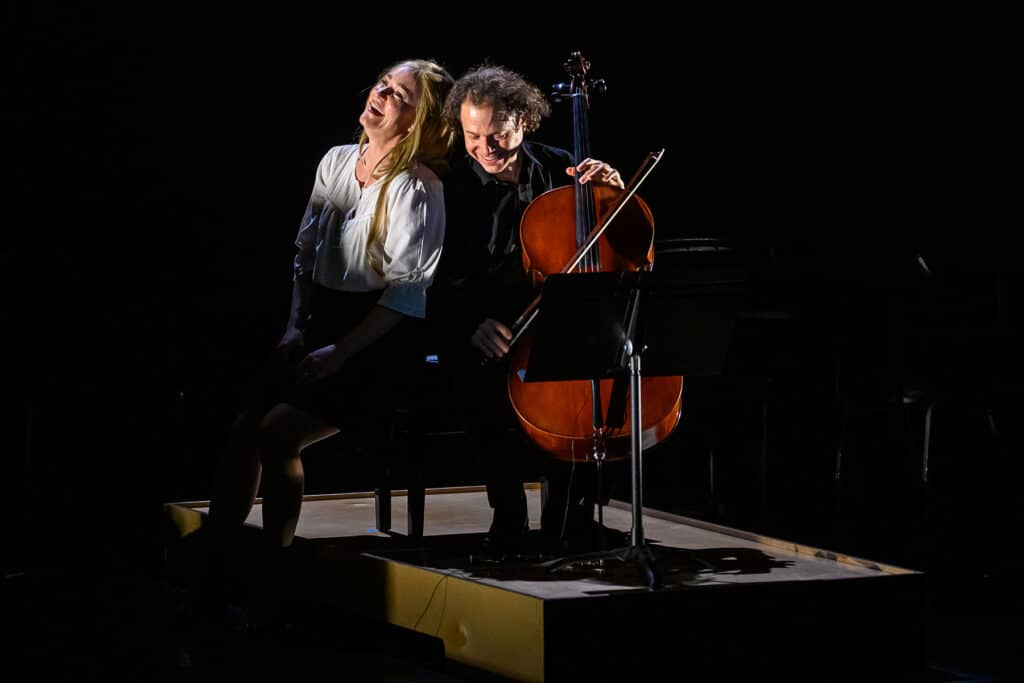 A singer and cellist on stage, laughing together