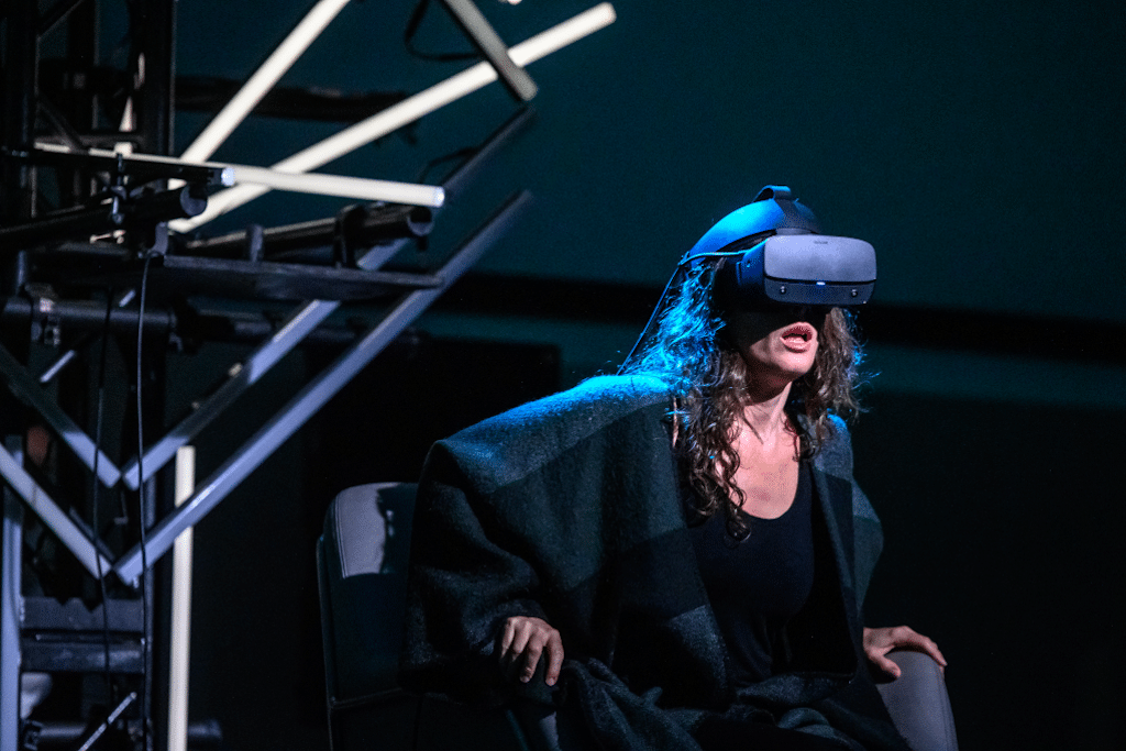 A photograph of a Tap:Ex Augmented Opera performance - a woman wears a VR headset