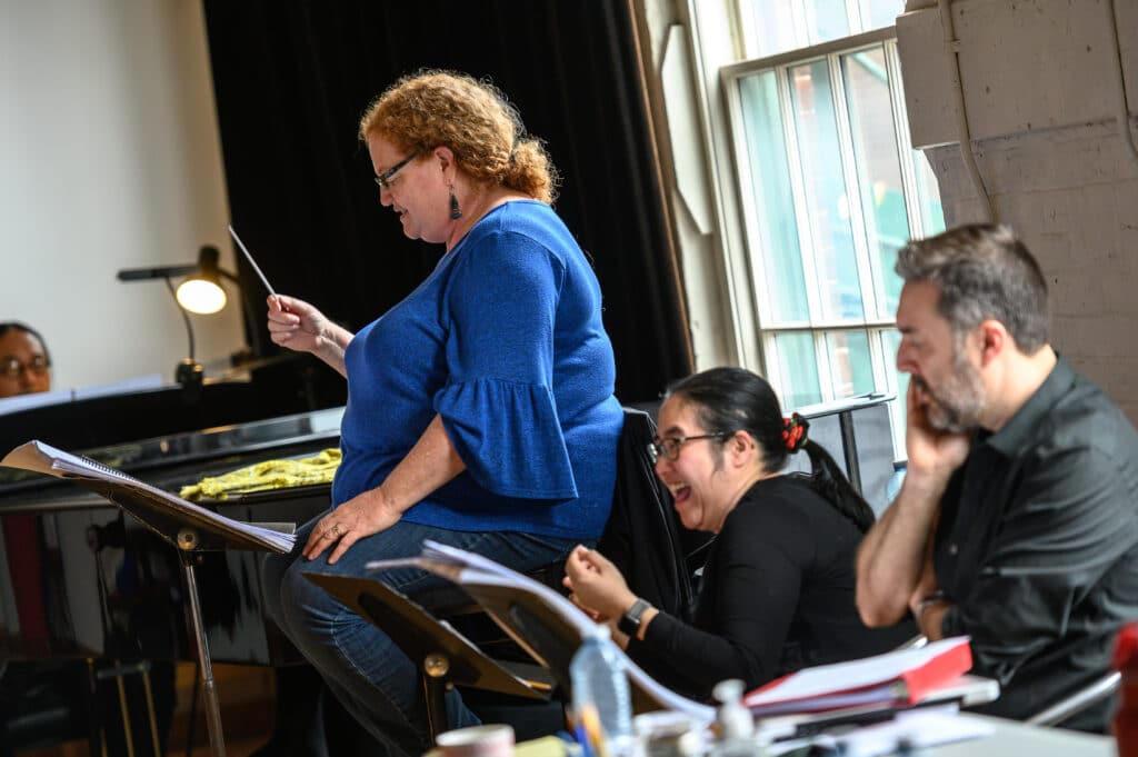 Conductor Rosemary Thomson holding a conductors baton rehearsing the opera Shawnadithit
