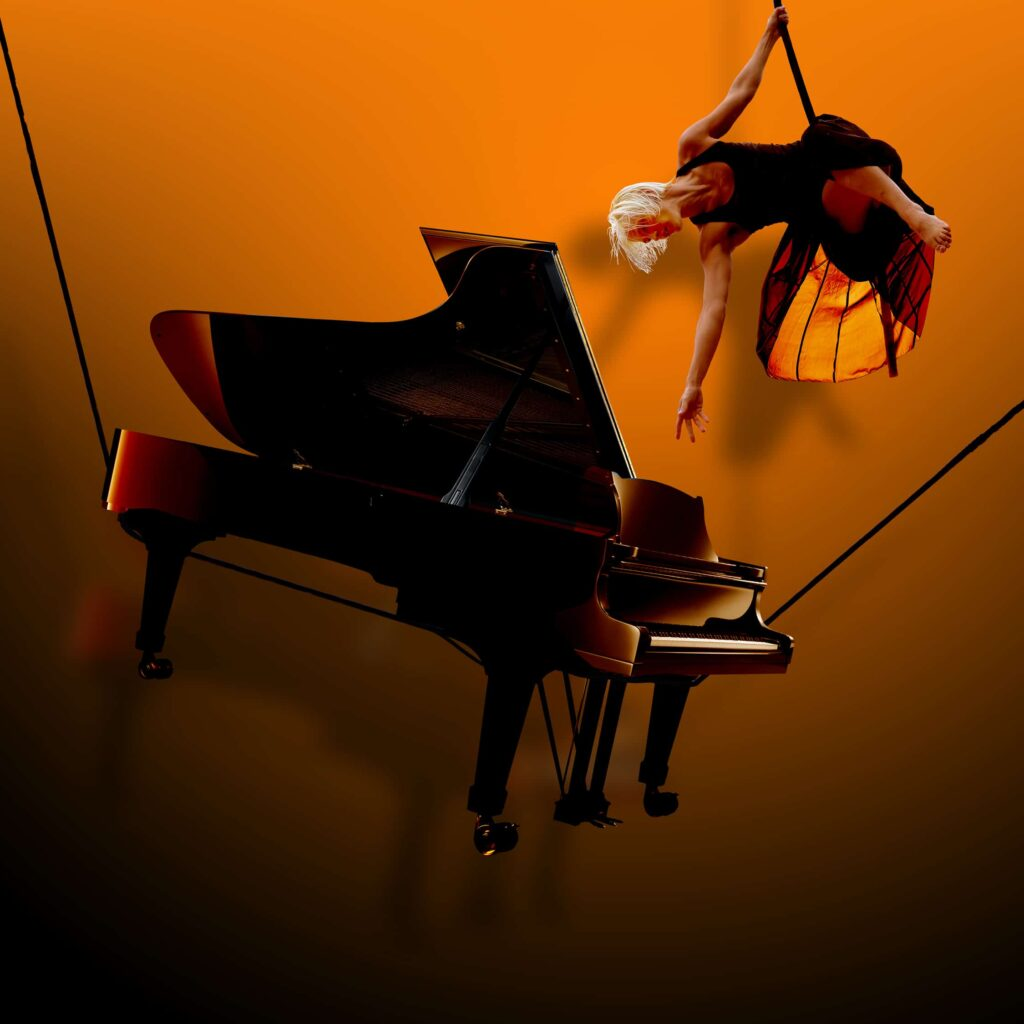 Gould's Wall: A woman suspended in the air reaching towards a piano, also suspended